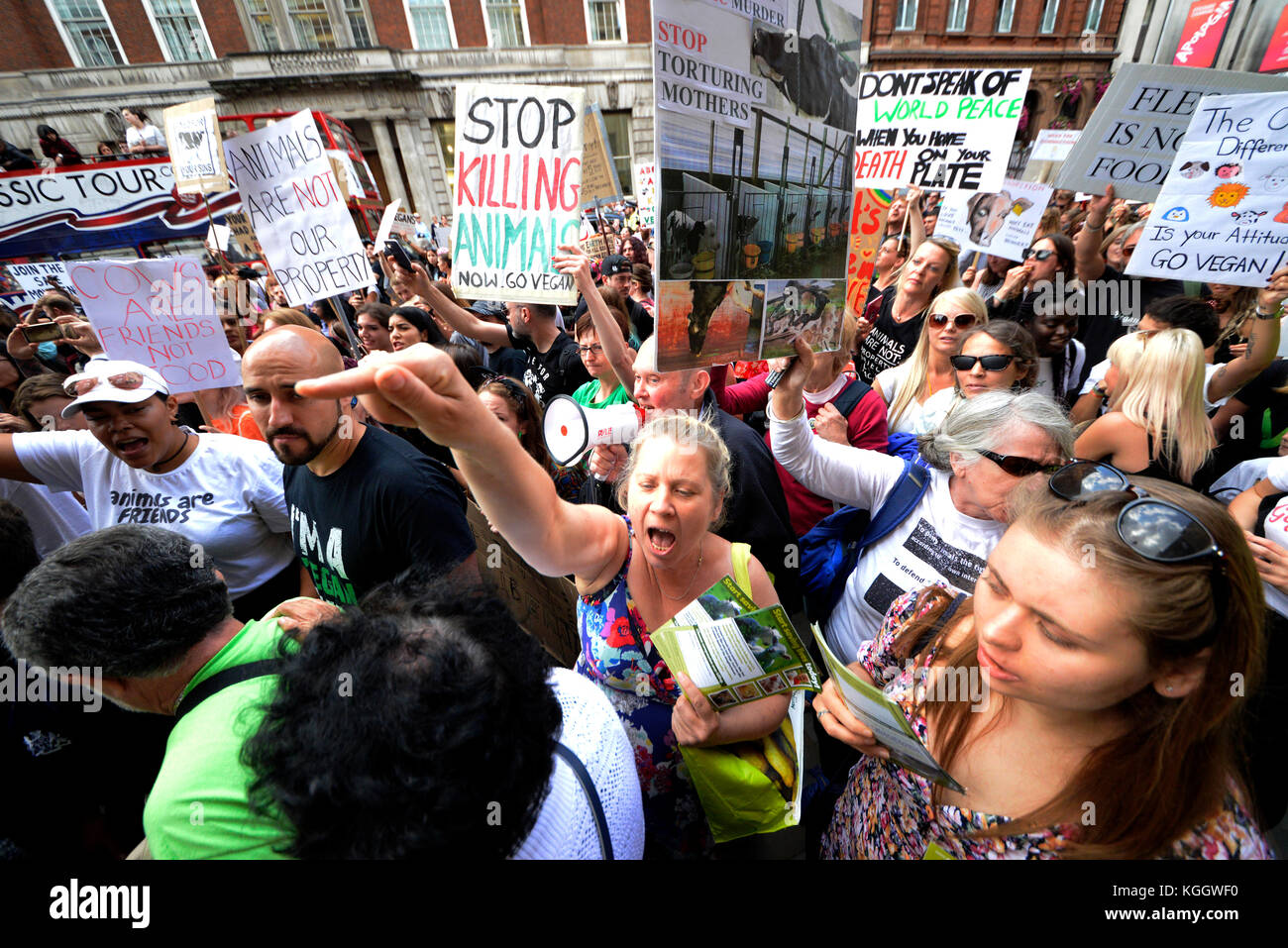 Vegan activists protesting in Whitehall London during an animal rights protest demonstration rally march. Placards. Stock Photo