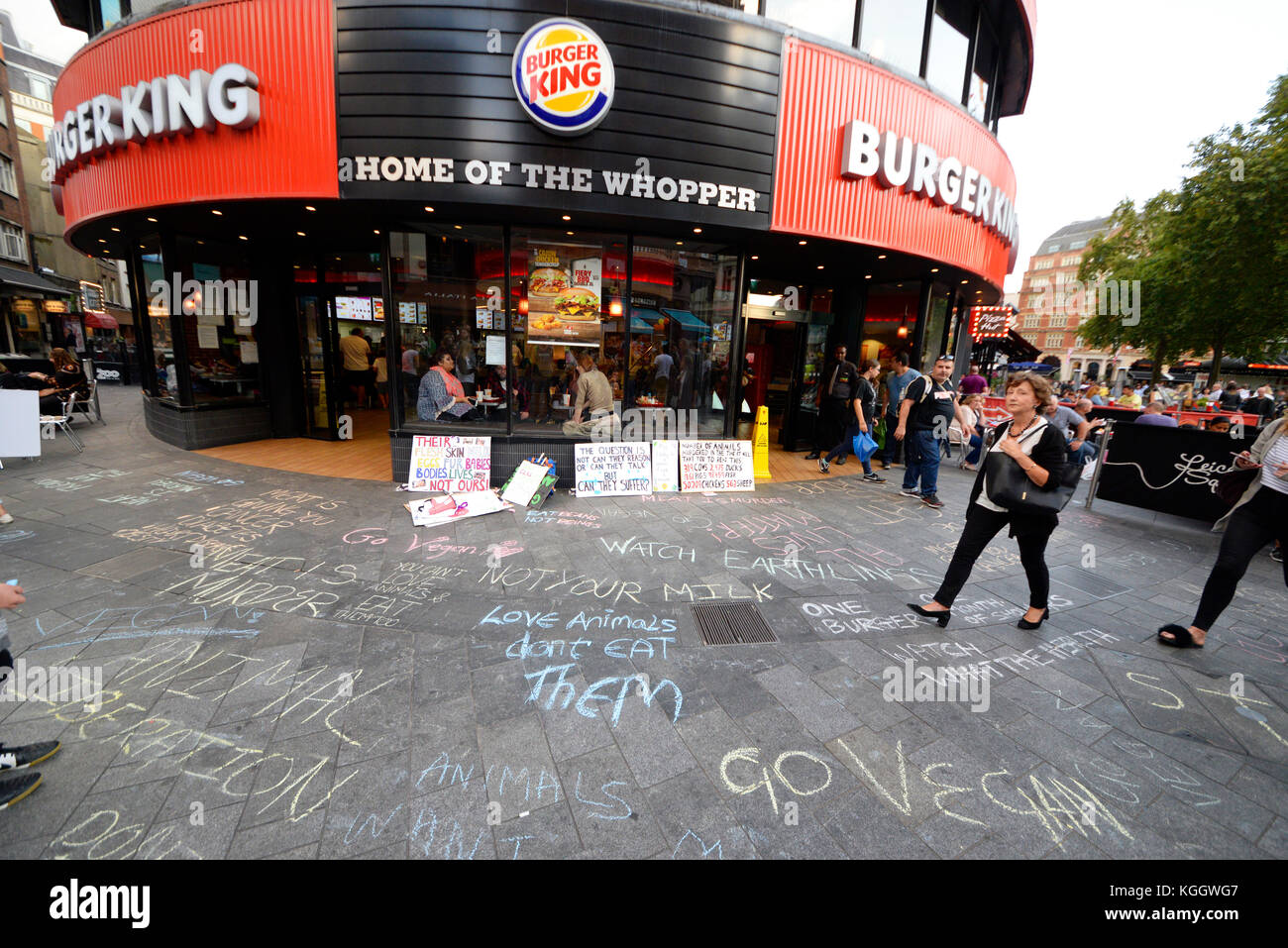 Animal rights activists protesting outside Burger King in Leicester Square, London. Chalk slogans on pavement. Woman - Stock Image