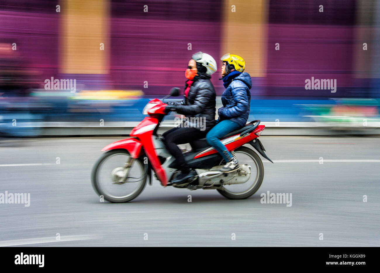 Panning shot of two Asian women zipping by on a scooter - Stock Image