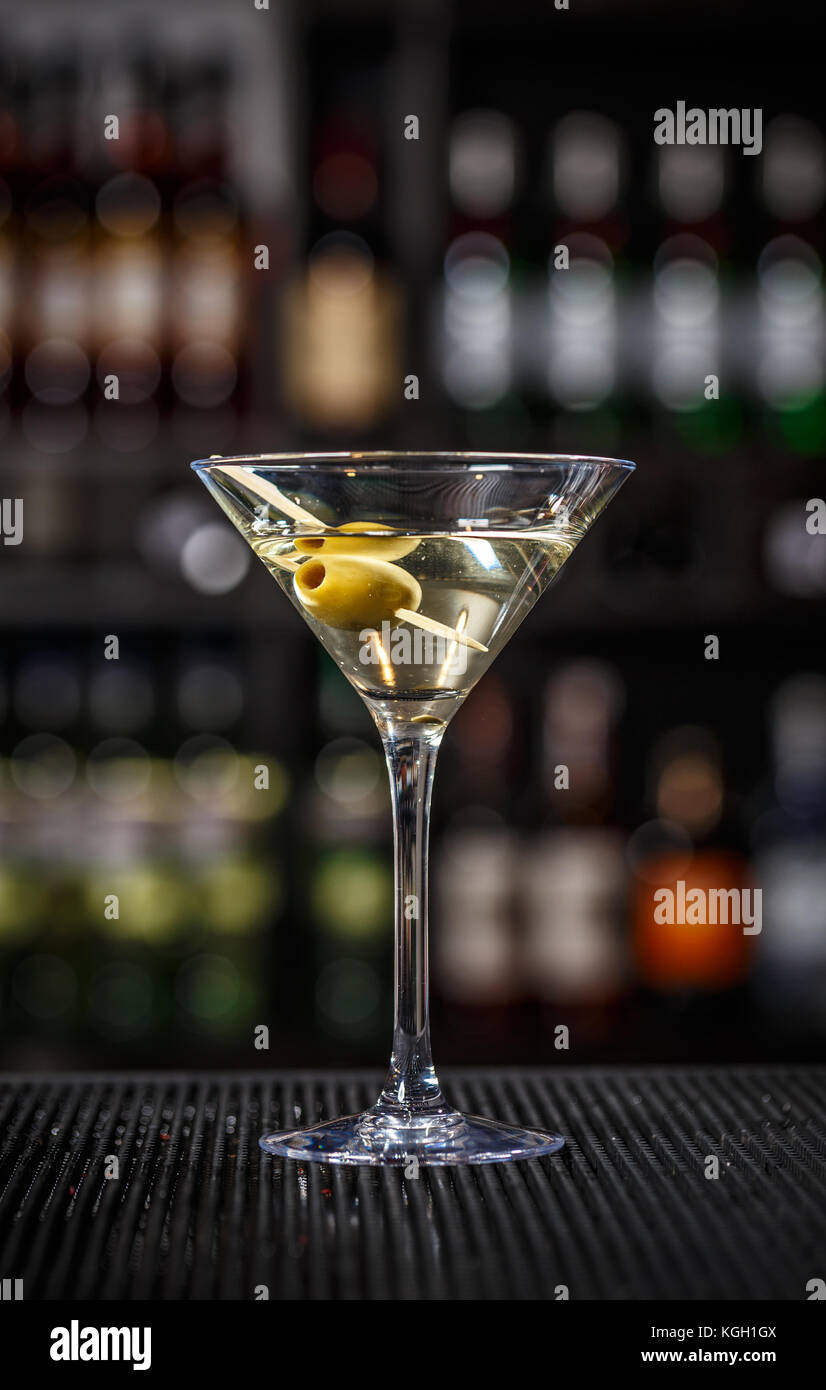 Martini cocktail with green olives on a bar counter - Stock Image