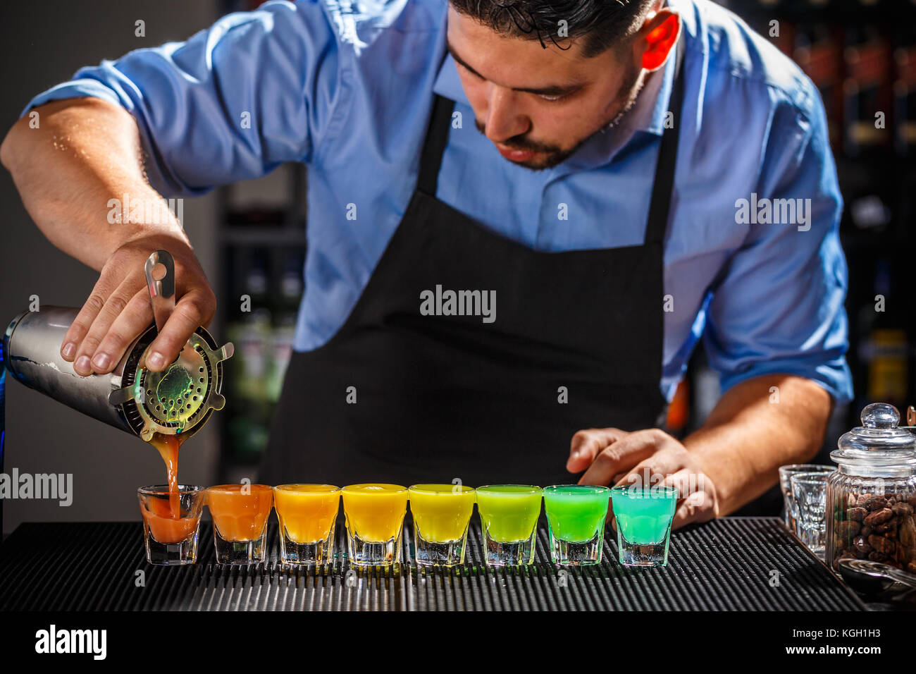 Dozen of colorful rainbow cocktails being prepared on the counter by a bartender - Stock Image
