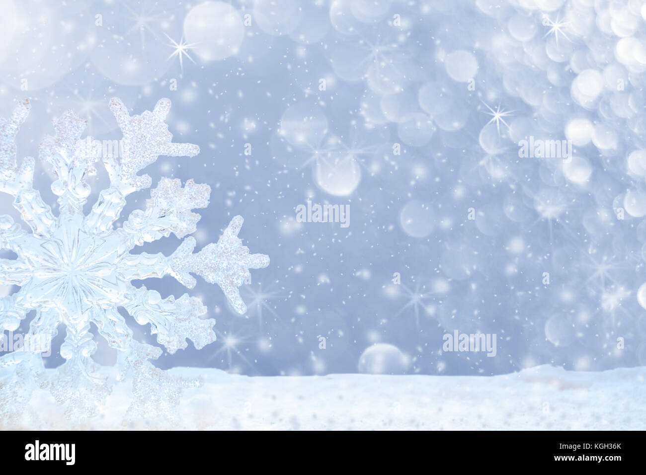 Big transparent snowflake in snow and beautiful bokeh with asterisks and snowfall. - Stock Image