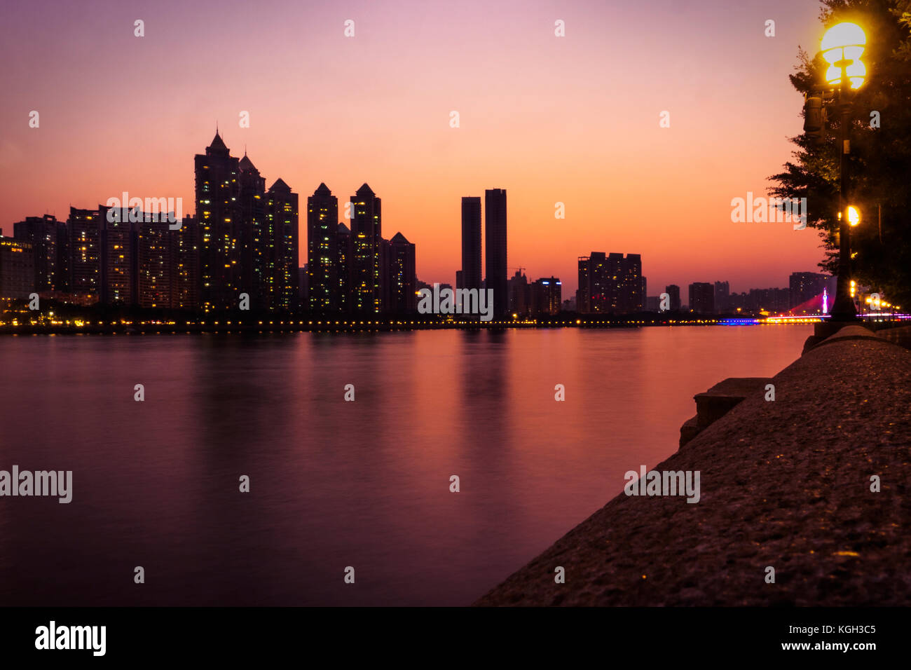 Dusk falls over the Pearl River and the City of Guangzhou, capital of Guangdong province. Luxury apartments are - Stock Image
