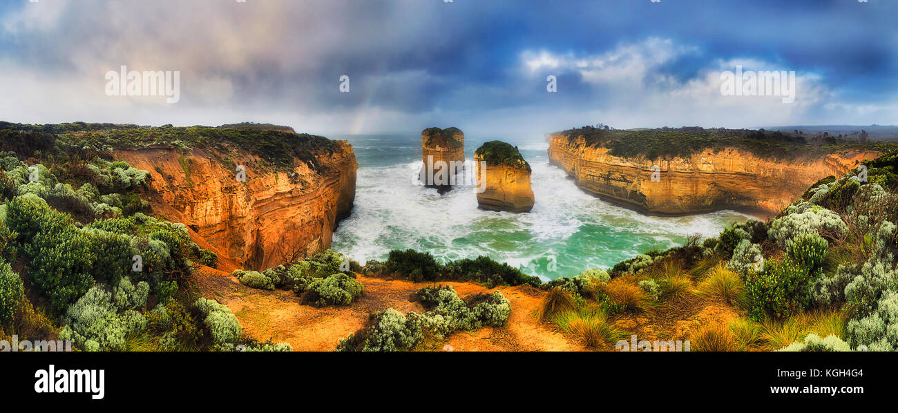 Rainbow over eroded limestone rock apostles at Loch Ard Gorge of Great Ocean road Twelve Apostles marine park. Stormy - Stock Image