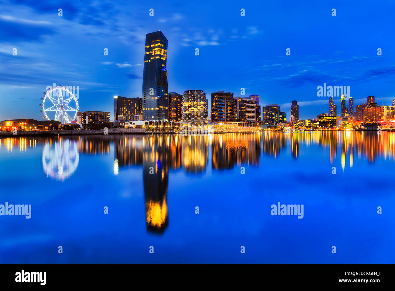 BLue dark sunset at Melbourne Dockalnds area with still Yarra river waters mirroring bright lights of modern ubran - Stock Image