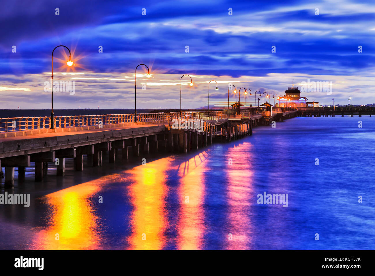 Stormy sunset at Port Philip bay around St Kilda beach historic timber Jetty with street light illumination reflecting - Stock Image