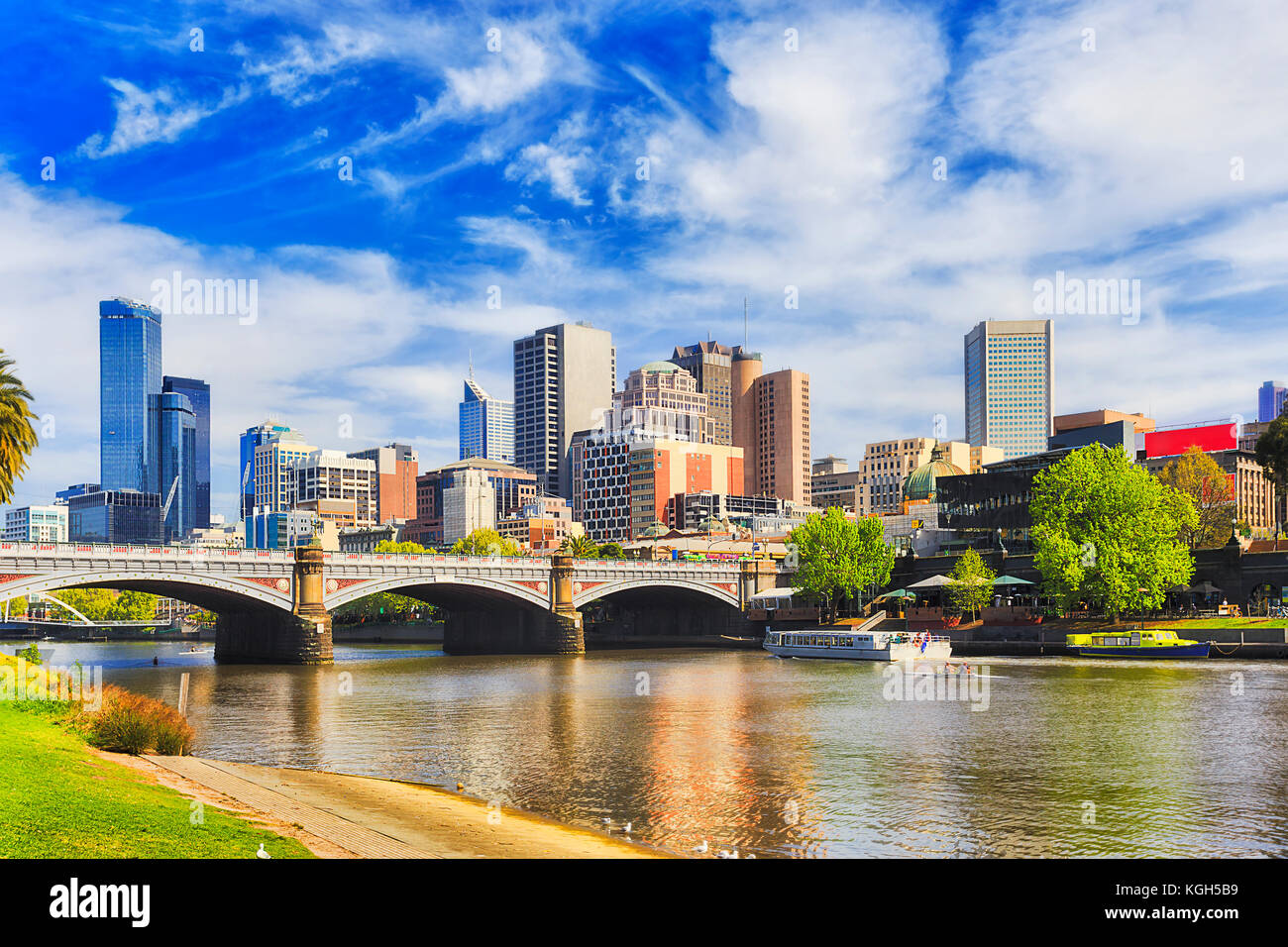 Princes bridge in Melbourne city across Yarra river on a sunny day in view of high-rise towers and modern urban architecture. Stock Photo