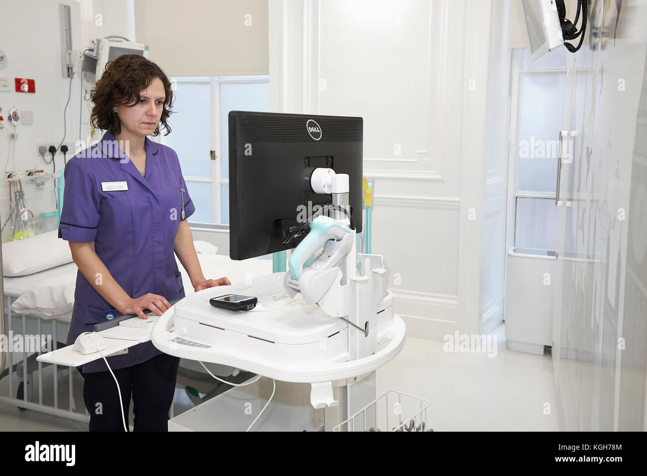 A Nurse checking information on a computer in a hospital. - Stock Image