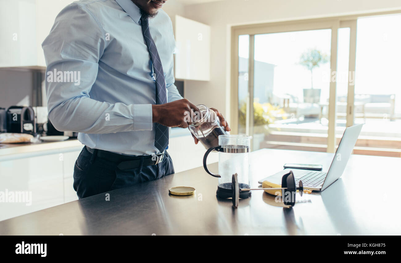 Man in formal clothes making coffee using French press with a laptop computer on kitchen table. Businessman preparing - Stock Image