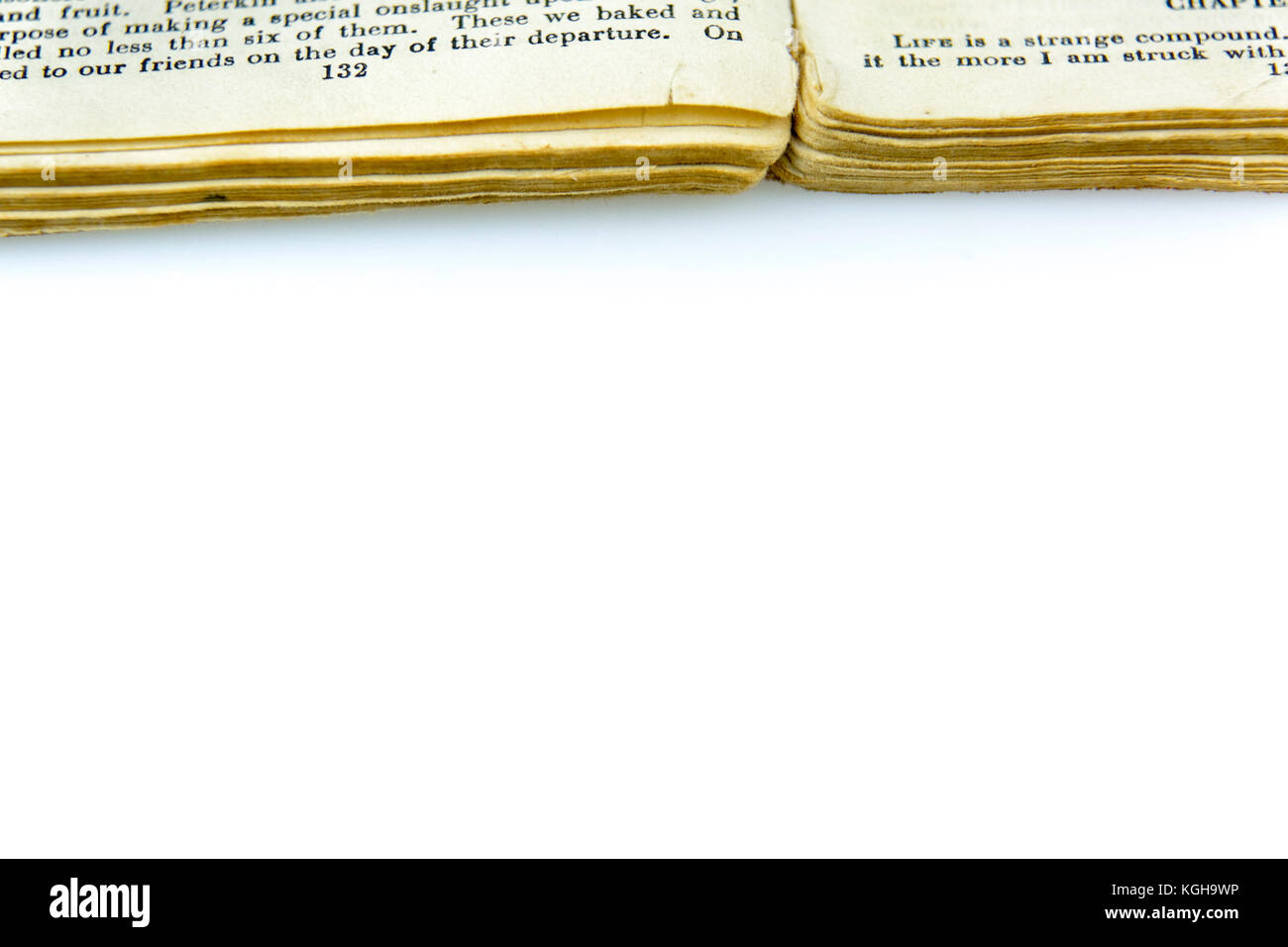 Old antique book with text and worn pages open on white. Vintage print publication background with copy space. Stock Photo