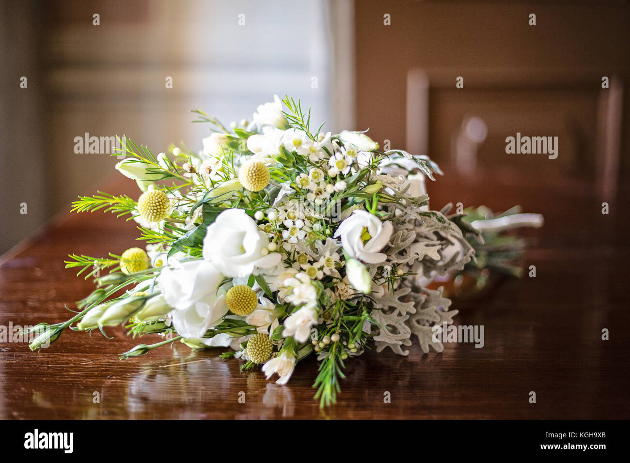 Rustical white and green wedding bouquet placed on a wooden table, indoors, next to the window, natural light - Stock Image
