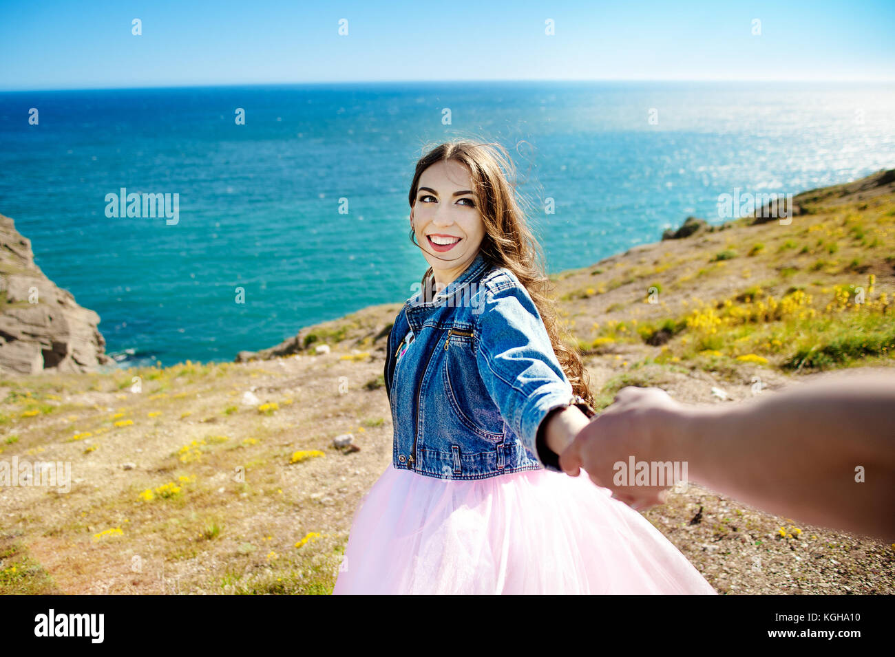 beautiful woman smiling and holding man by hand and going to the lake in the mountains at glowing sunrise - Stock Image