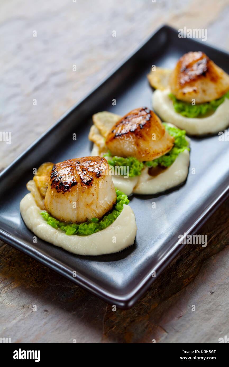 Scallops with jerusalem artichoke puree and pea mash - Stock Image
