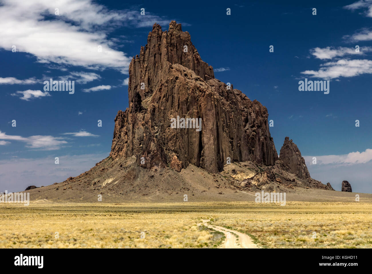 Volcanic Plug, Shiprock, NM Shiprock is composed of fractured volcanic breccia and black dikes of igneous rock called - Stock Image