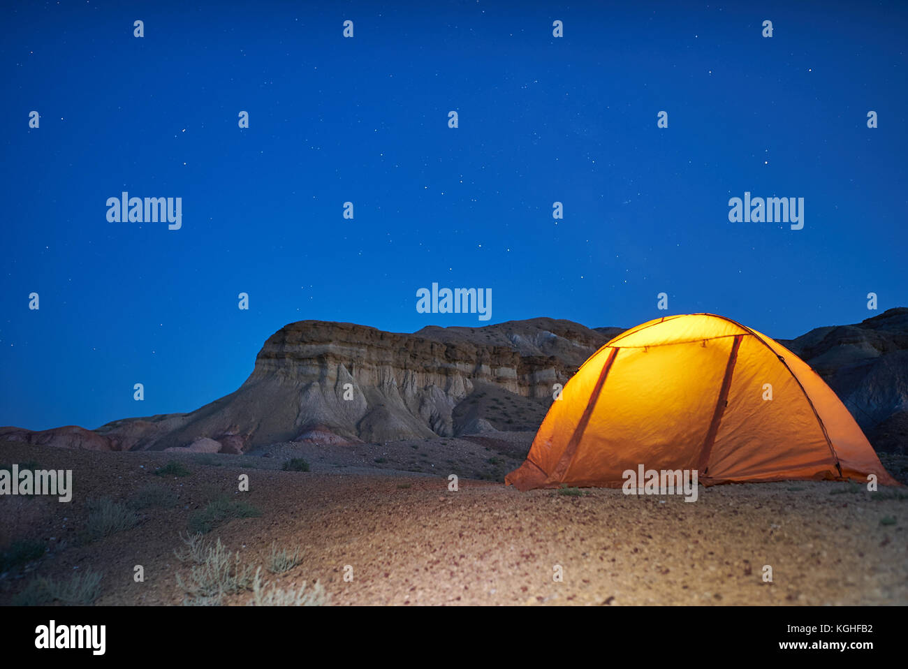 Lonely evening camping in Mongolian canyons. yellow illuminated tent is located near canyons - Stock Image