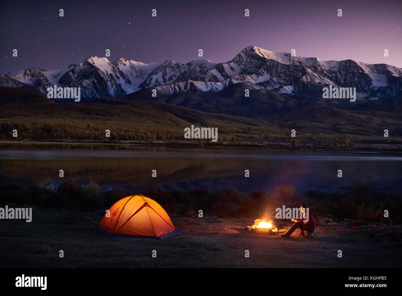 Night camping. Man tourists sitting in the illuminated tent near campfire under amazing sunset evening sky in a - Stock Image