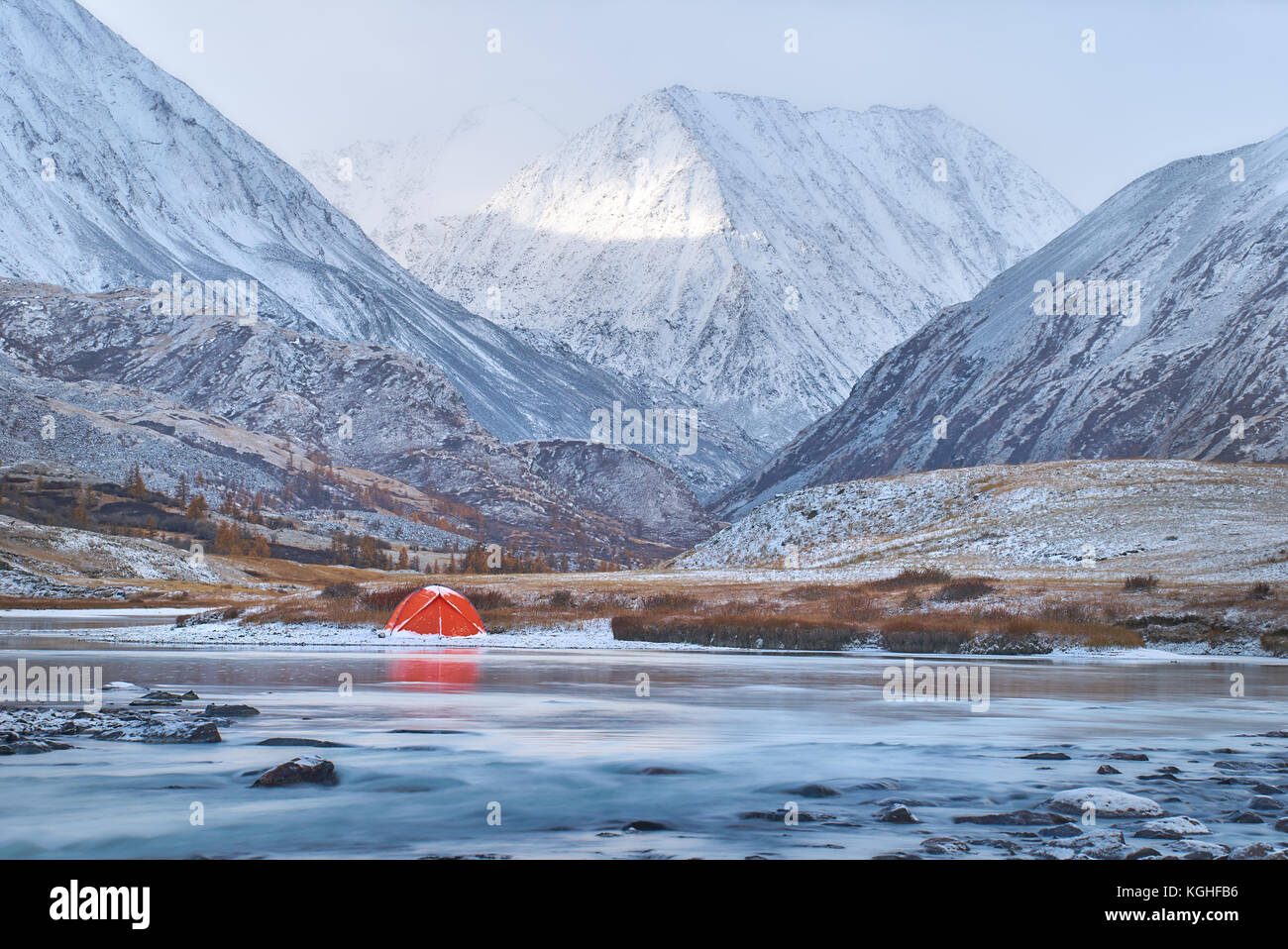 Winter or late fall in mountains, lonely camping and a river or a lake. Red tent is located on the river bank. terrain - Stock Image
