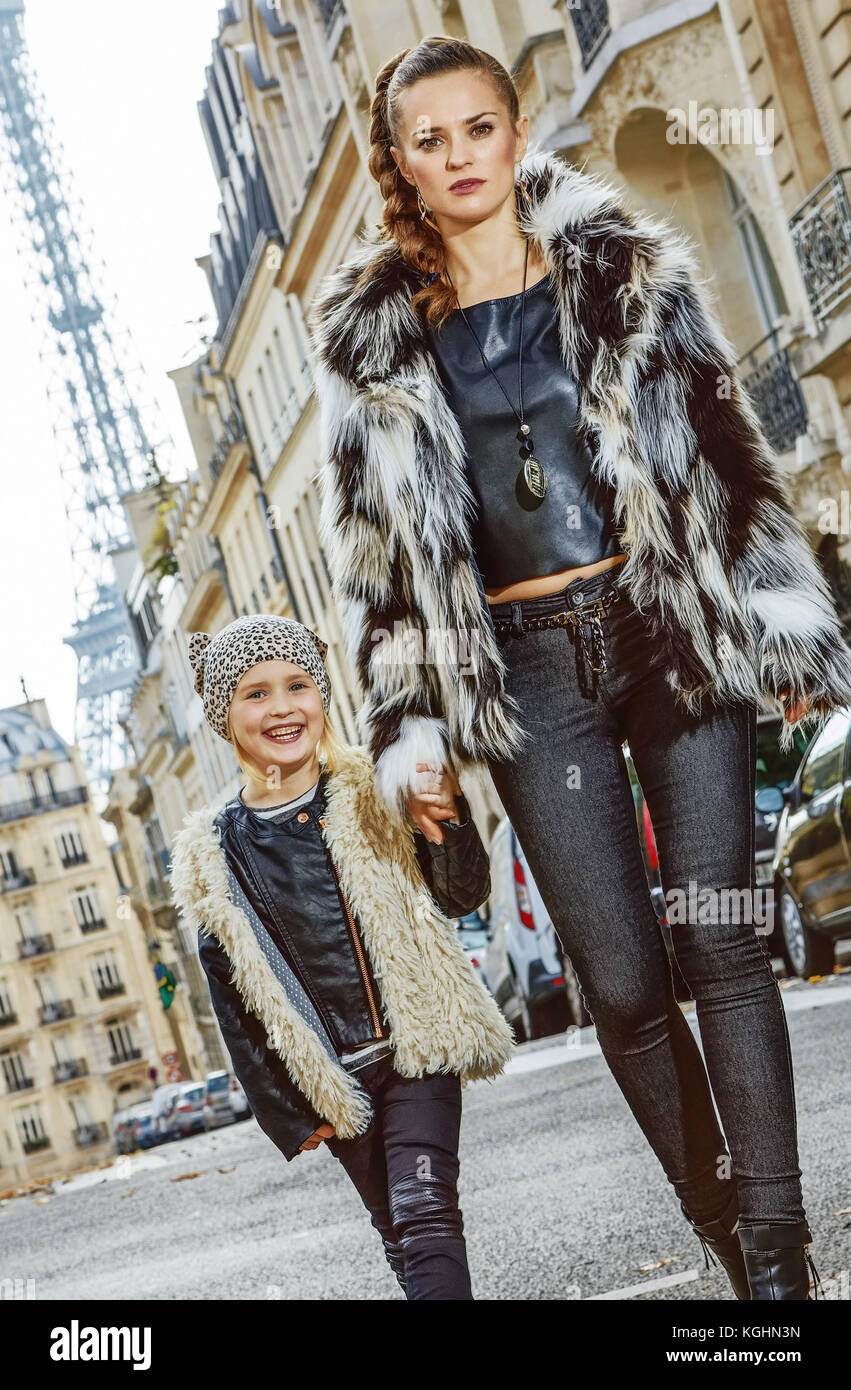 Boiling hot trendy winter in Paris. modern mother and daughter in Paris, France going forward - Stock Image