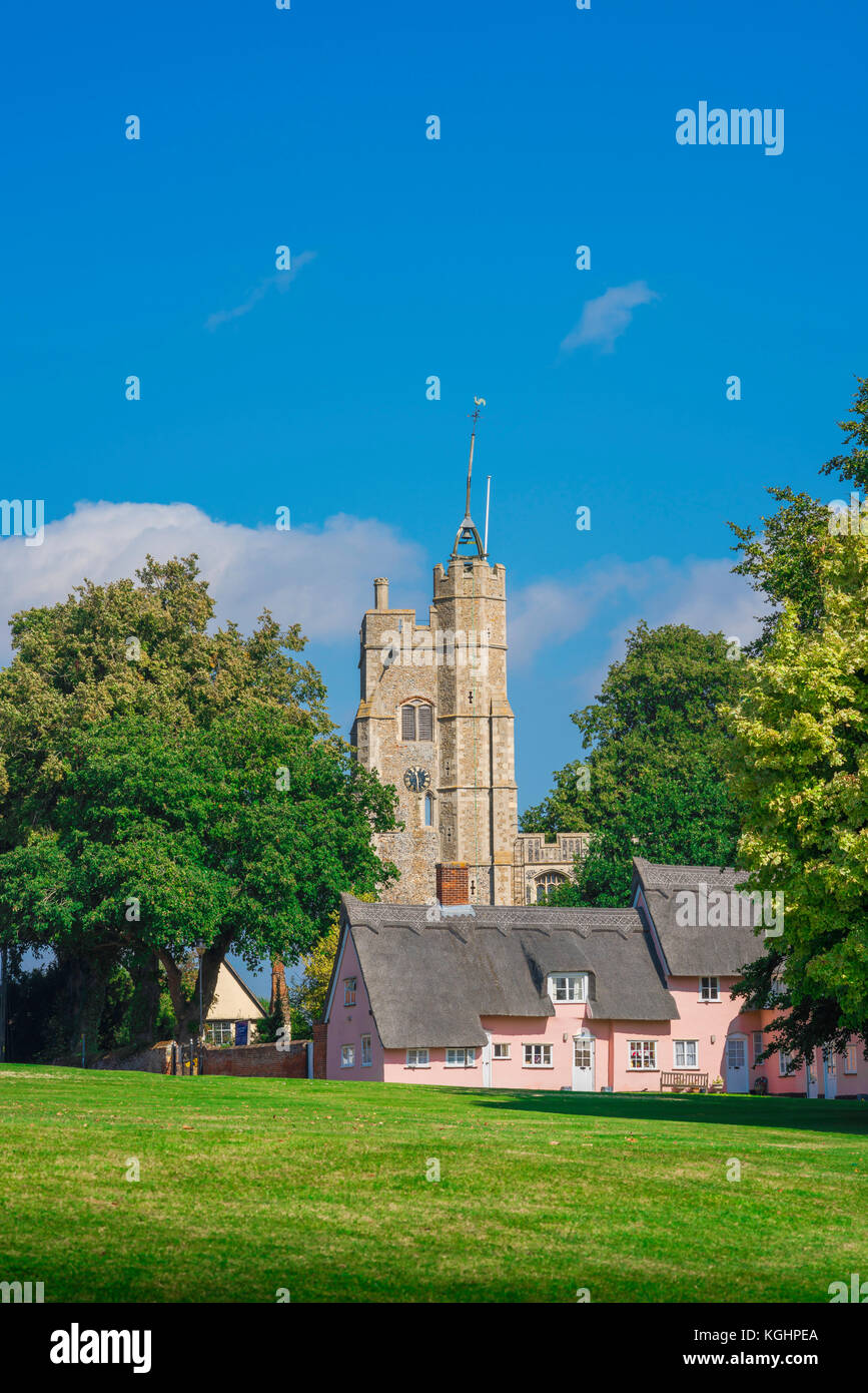 Village green England, view across the village green towards the church tower and traditional pink cottages in Cavendish, - Stock Image