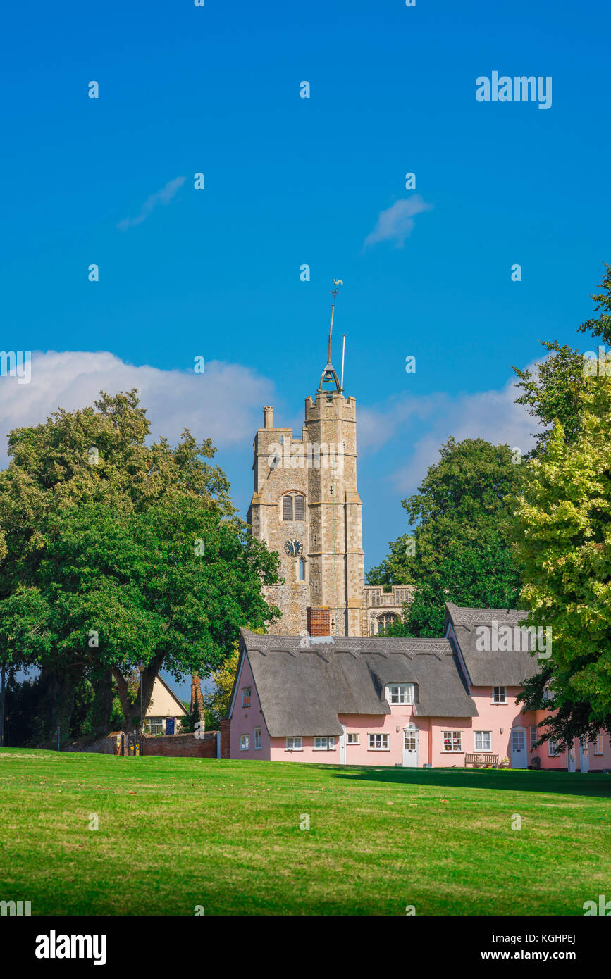 Cavendish Suffolk, the village green in Cavendish with the medieval church tower and cluster of traditional pink - Stock Image