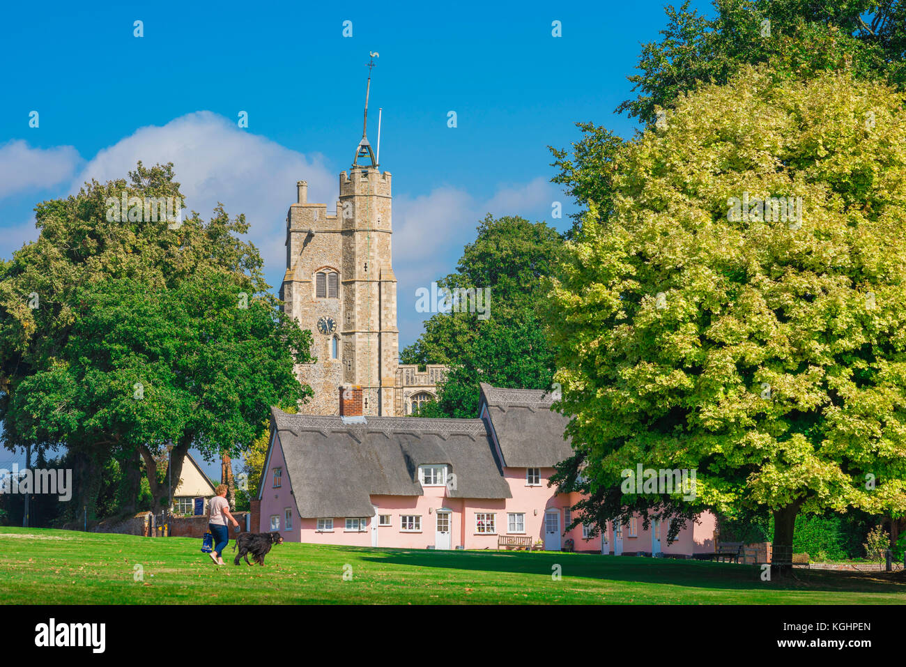 Village green UK, view across the village green towards the medieval church tower and traditional pink cottages - Stock Image