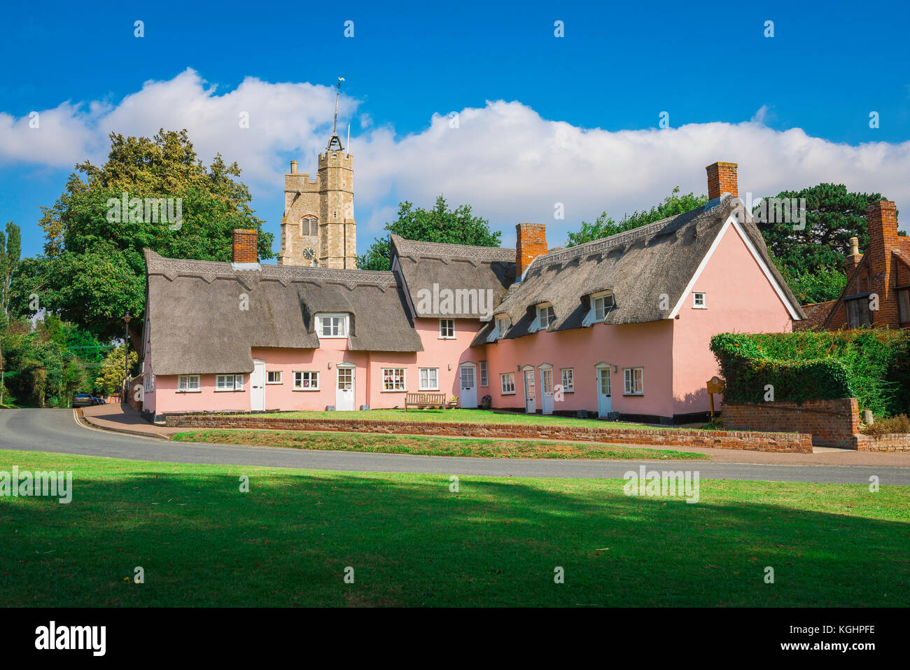Suffolk village UK, view across the village green of a group of traditional pink cottages in Cavendish, Suffolk, - Stock Image
