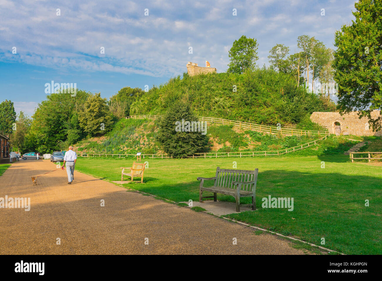 Clare Castle Suffolk, a man walks his dog in Clare Castle Country Park with Norman motte and bailey castle in the - Stock Image