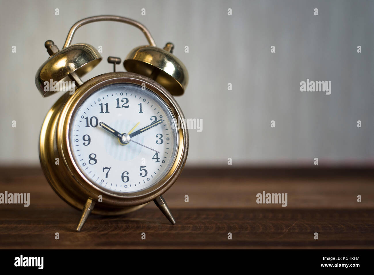 golden time clock - Golden bell clock on a wooden table background - Stock Image