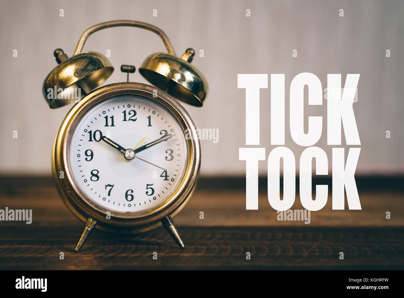 "tick tock day concept - golden bell clock on a wooden table background with ""Tick Tock"" word Stock Photo"