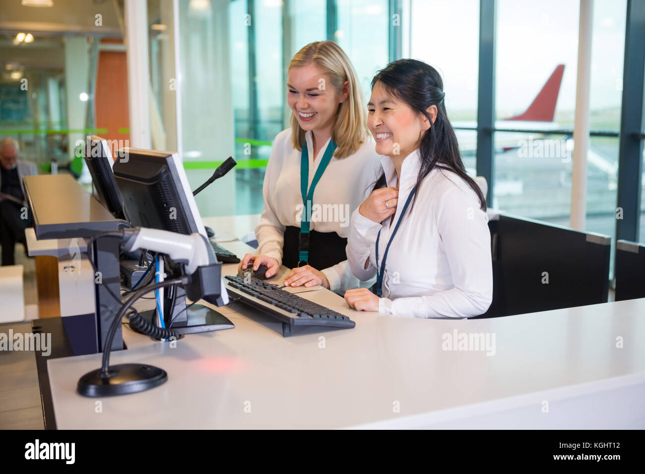 Smiling Receptionists Working At Desk In Airport - Stock Image