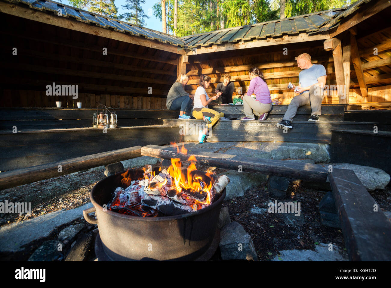 Burning Firepit With Friends Preparing Meal In Shed - Stock Image