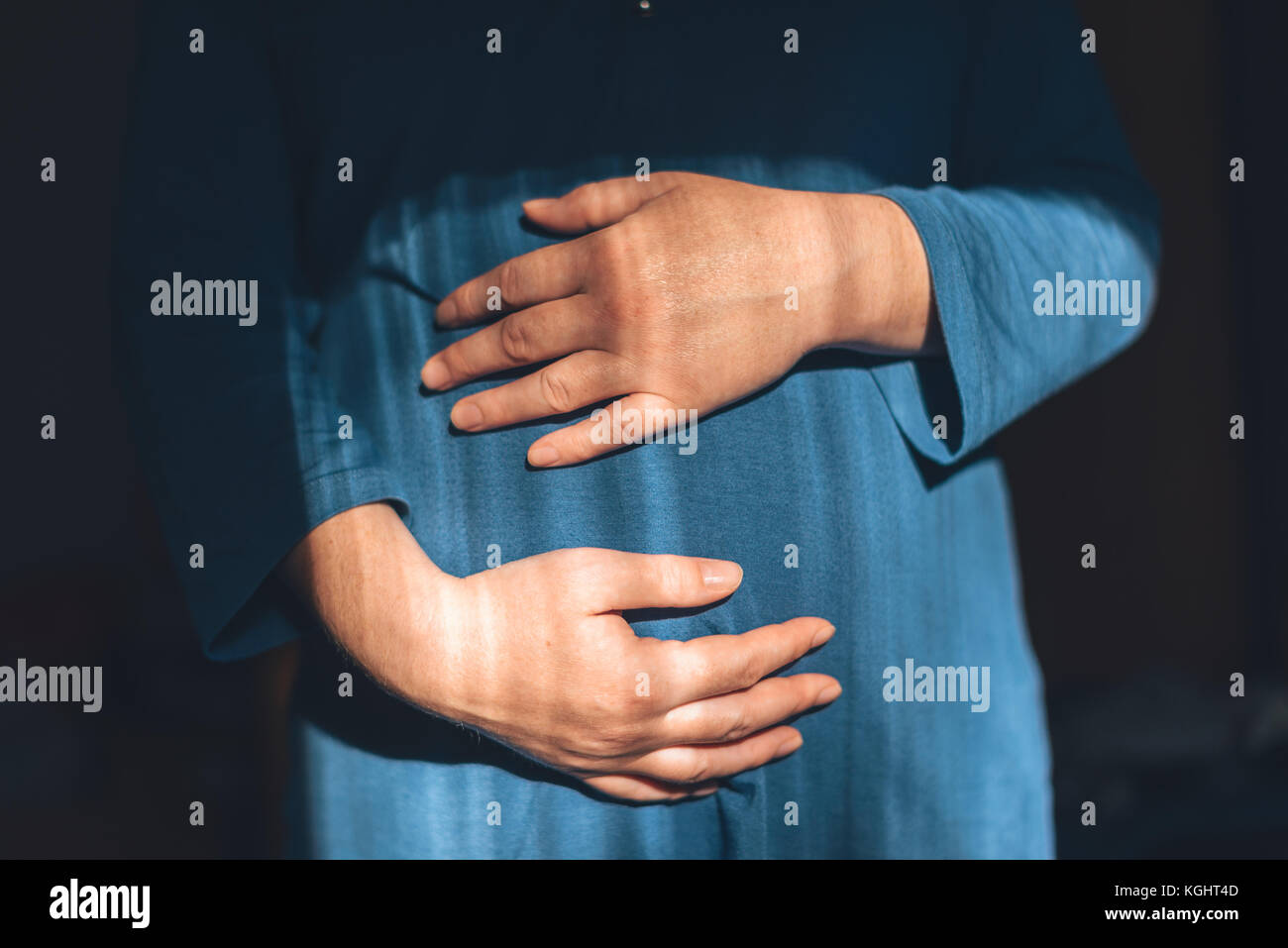 Gentle loving pregnant female with hands on her belly in third trimester of pregnancy expecting newborn baby - Stock Image
