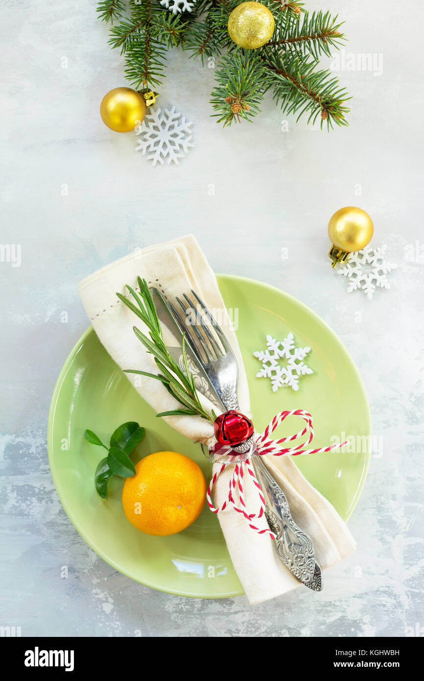 Holiday background. Decor Christmas table on stone or slate background. Green plate, cutlery and decorations. Top - Stock Image