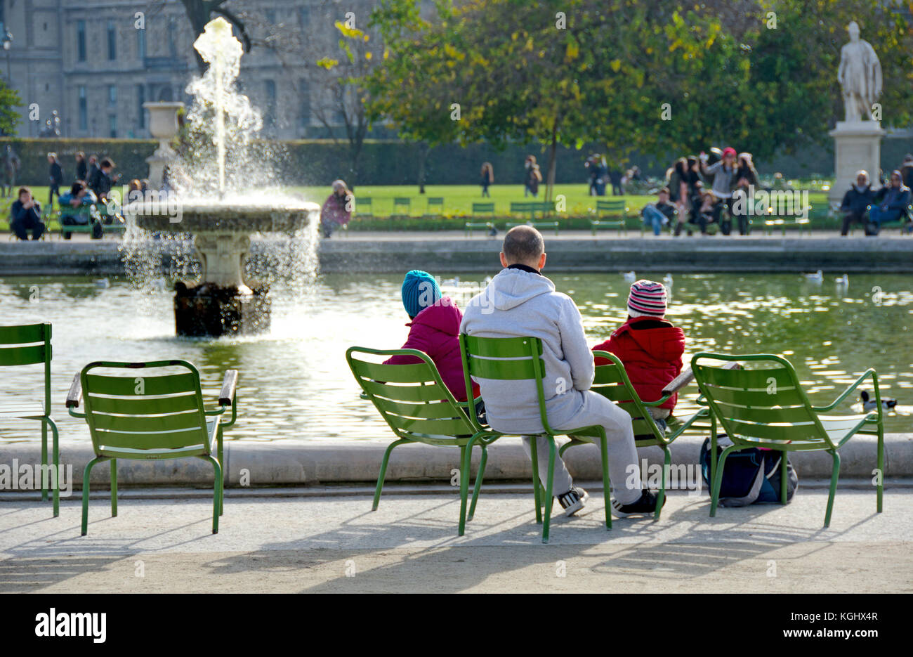 Paris, France. Jardin des Tuileries. Man with his young family by the Bassin Octagonal (pond) - Stock Image