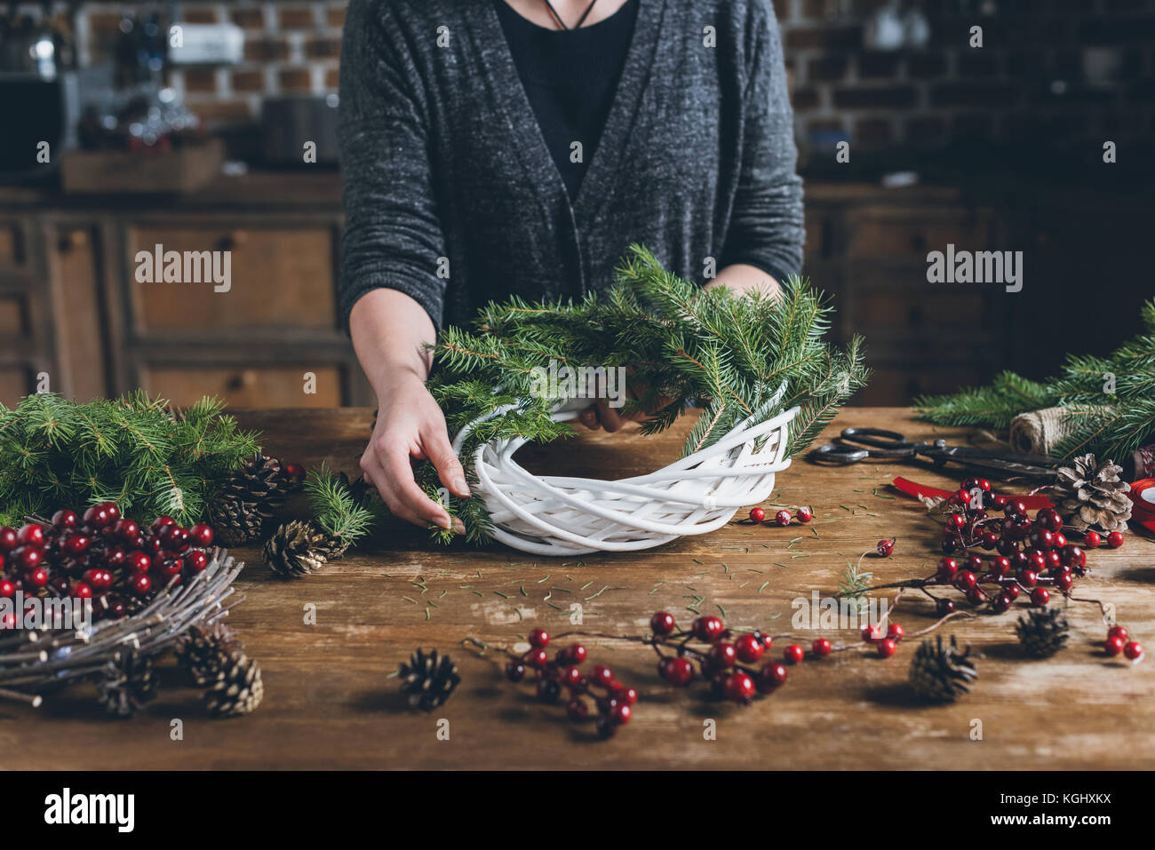 florist making Christmas wreath  - Stock Image