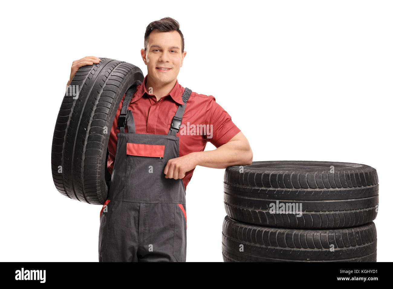 Mechanic leaning on a stack of tires isolated on white background - Stock Image