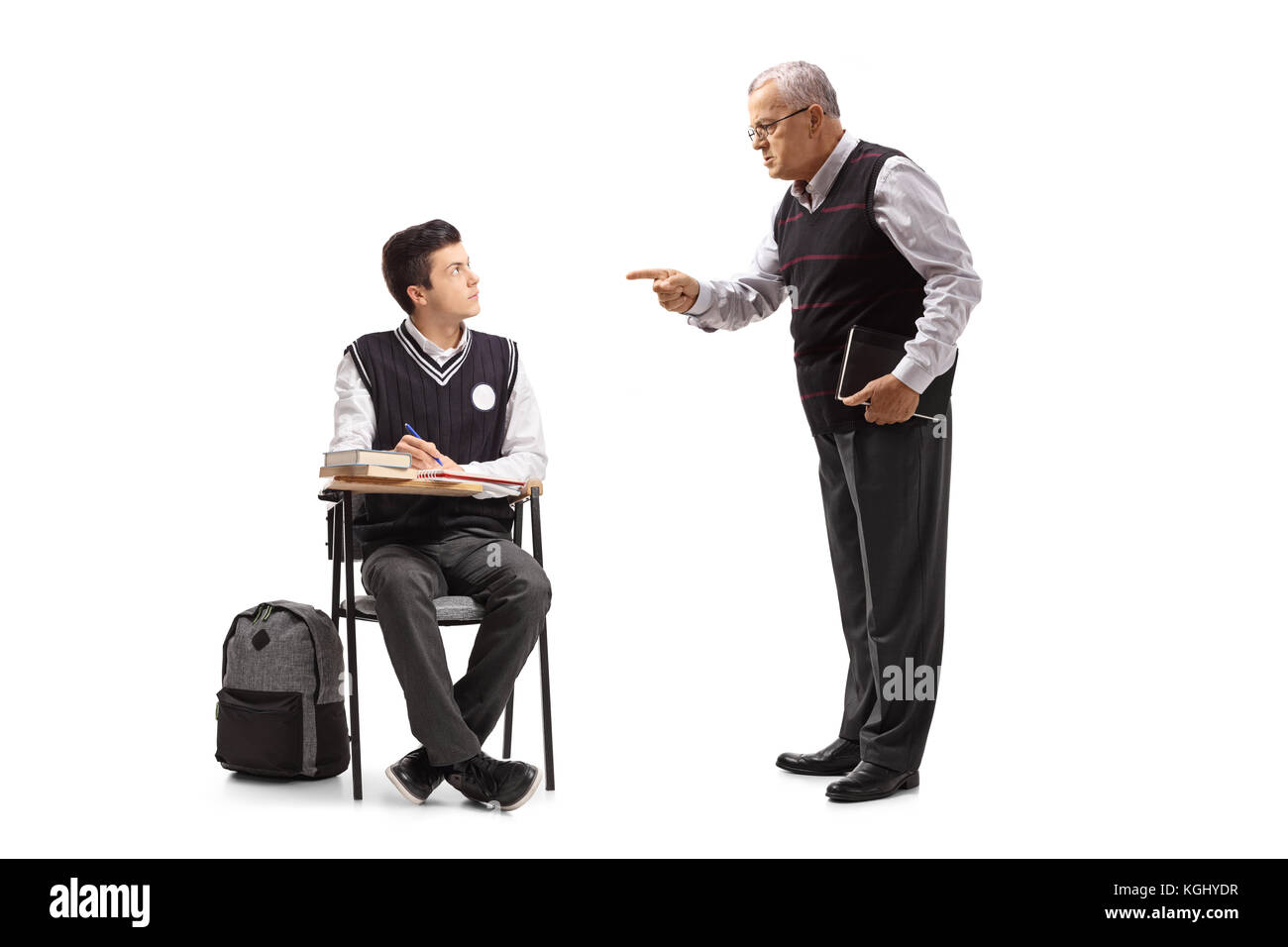 Teacher scolding a teenage student seated in a school chair isolated on white background - Stock Image