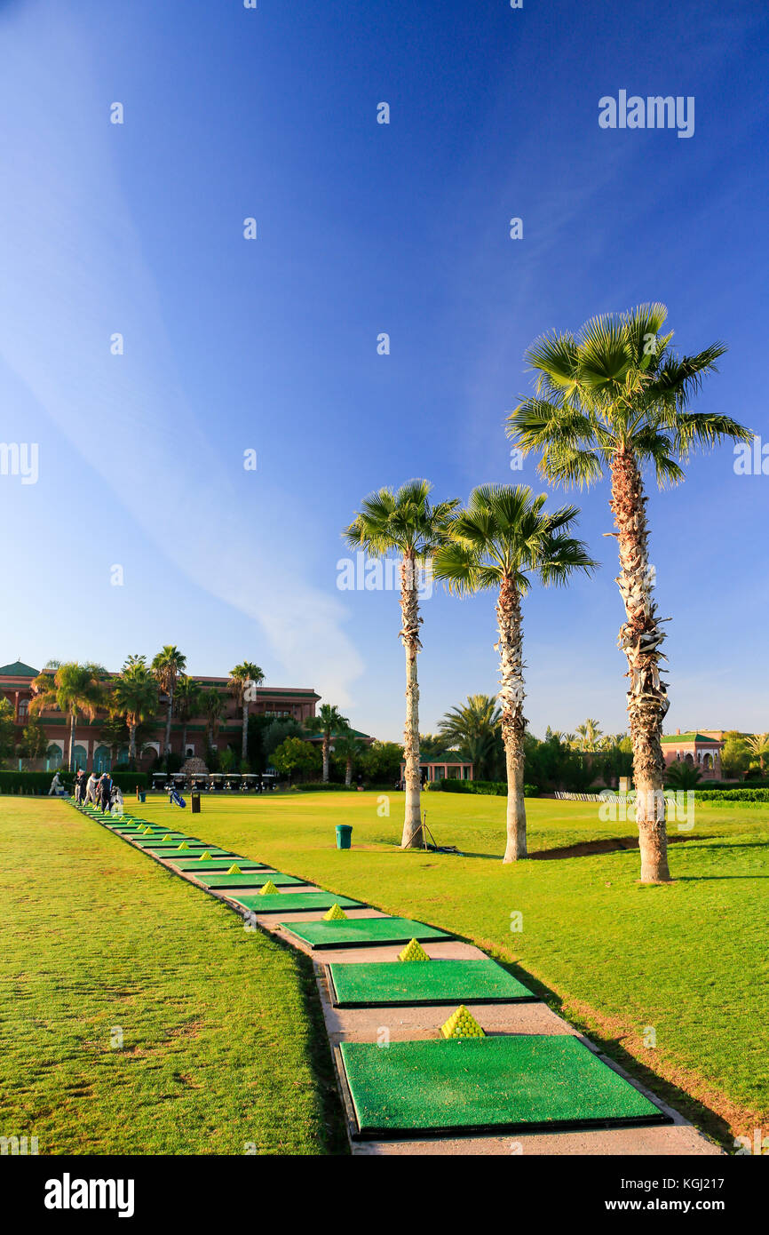 Open air golf driving range in Morocco with mats, piles of balls, palm trees and blue sky. Portrait. No people. Stock Photo