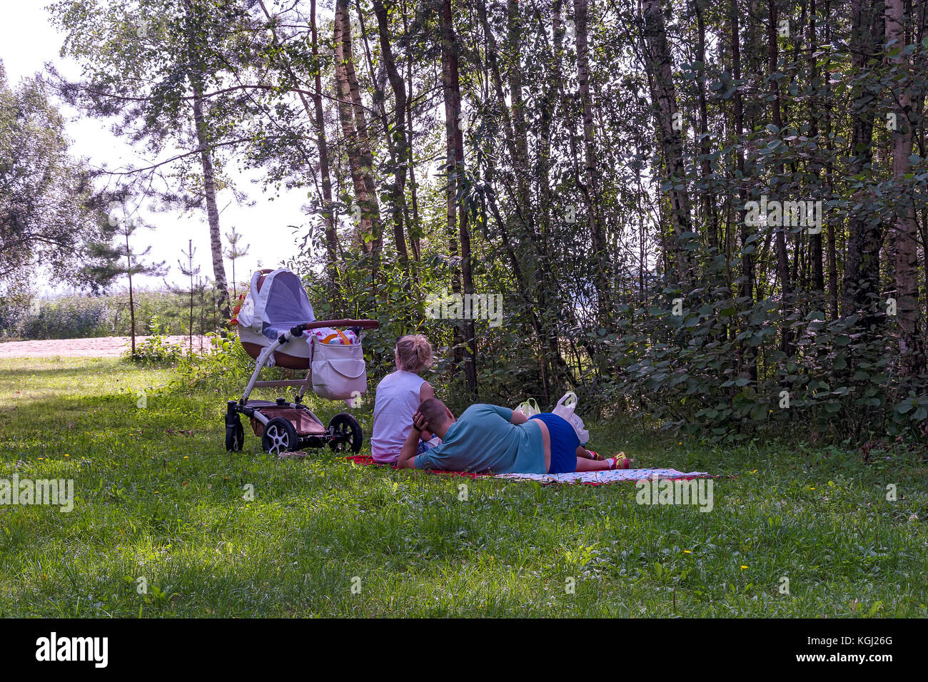 Family with a stroller resting in the shade of trees in the fresh air - Stock Image
