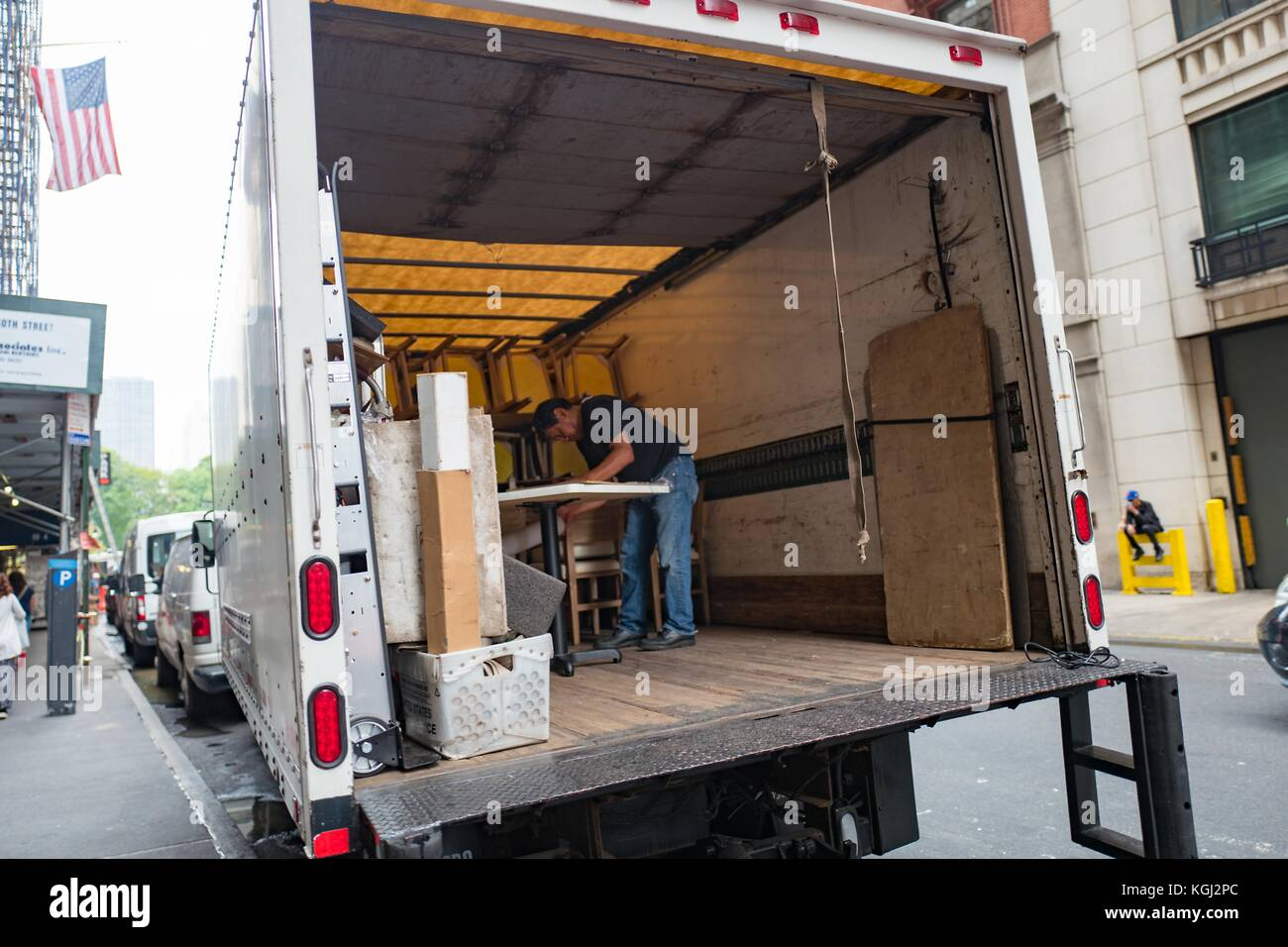 On a busy street in Manhattan, New York City, New York, a man assembles a table in the back of a delivery truck - Stock Image