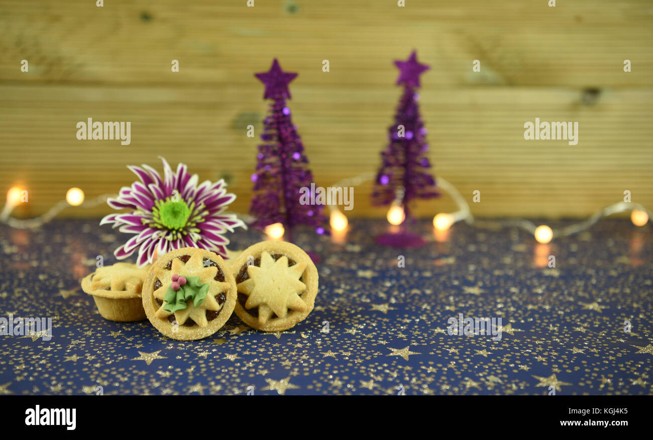 Christmas food photography image of traditional English mince pies with winter flower and glitter tree decorations - Stock Image