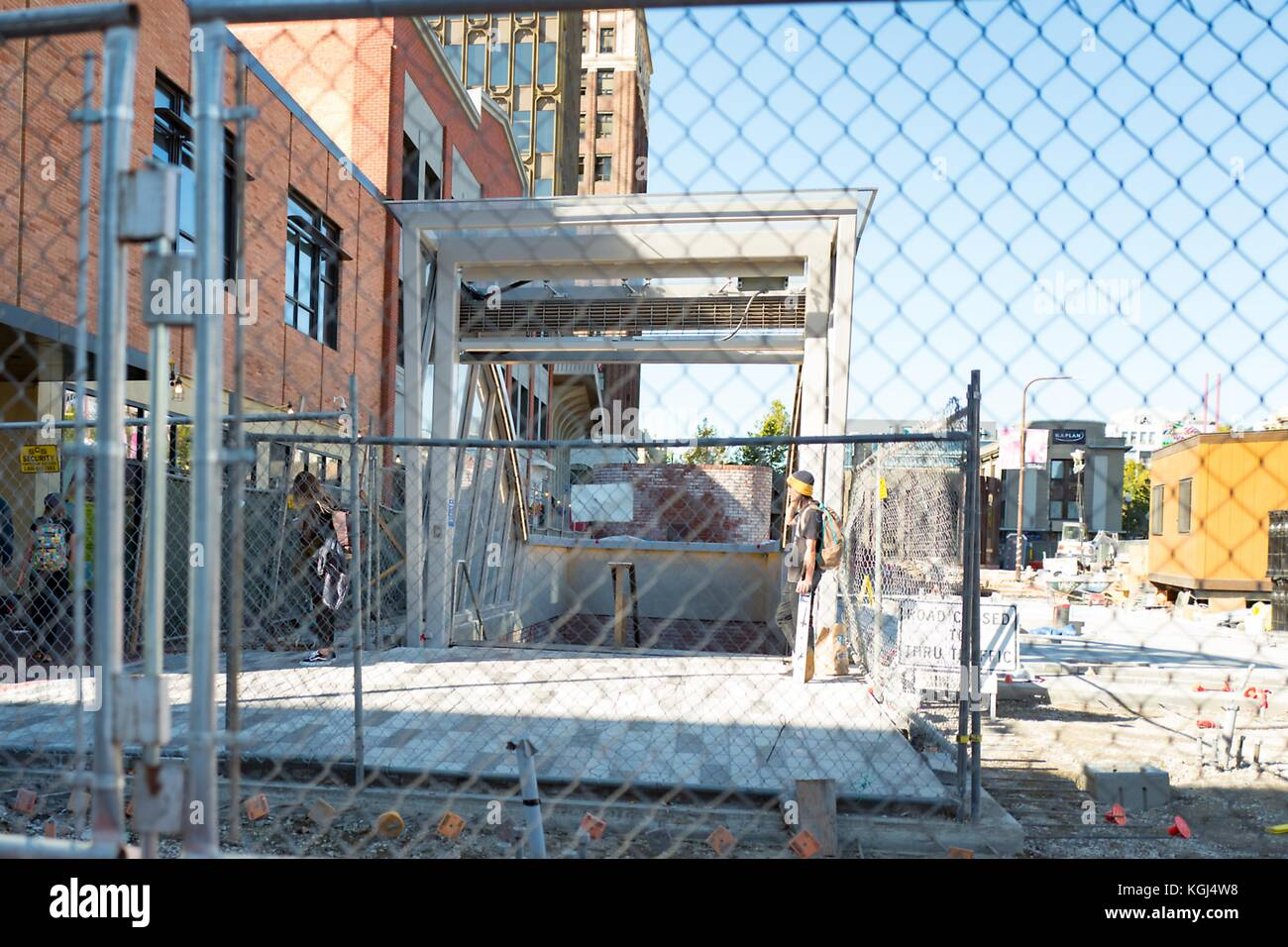 View through multiple chainlink construction fences to the entrance of the Bay Area Rapid Transit (BART) station - Stock Image
