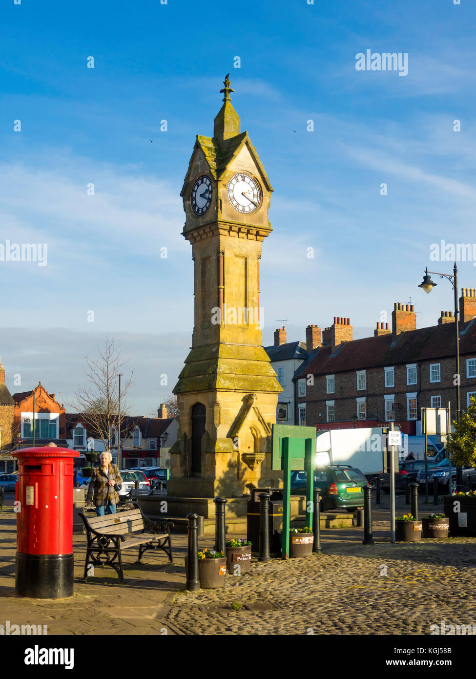 The town clock and a bright red Post Box in the Market Place in Thirsk North Yorkshire UK - Stock Image