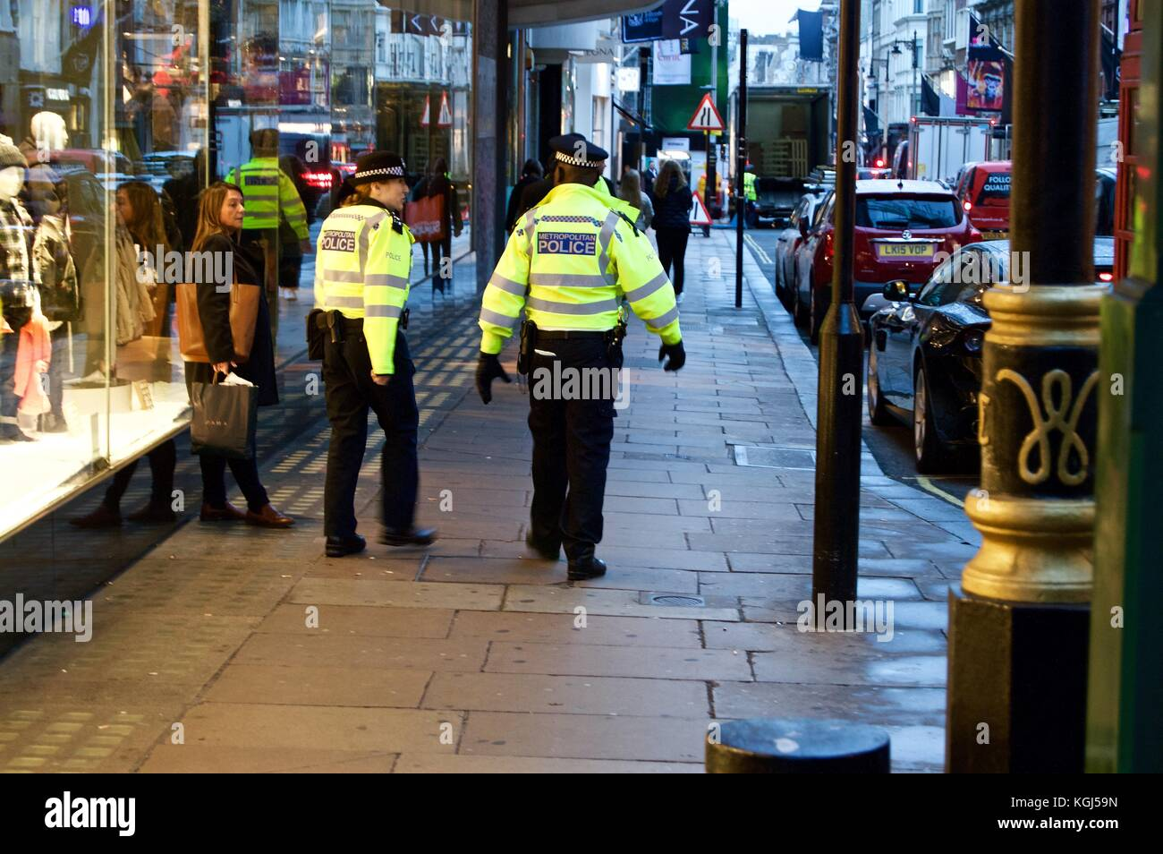 Police officers, one make and one female, New Bond Street, Christmas 2017, London, UK - Stock Image