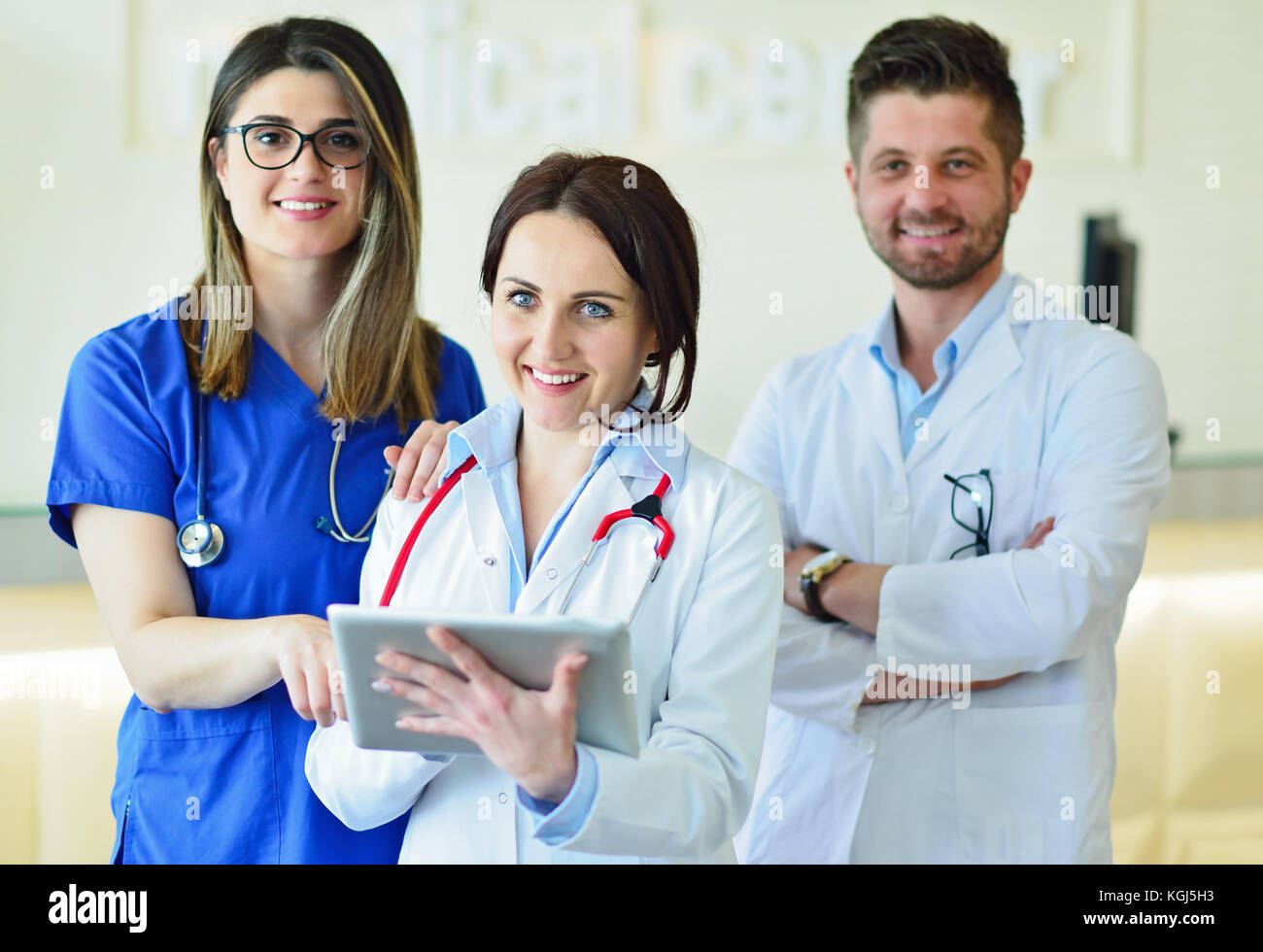 Young Attractive female doctor in front of medical group. - Stock Image