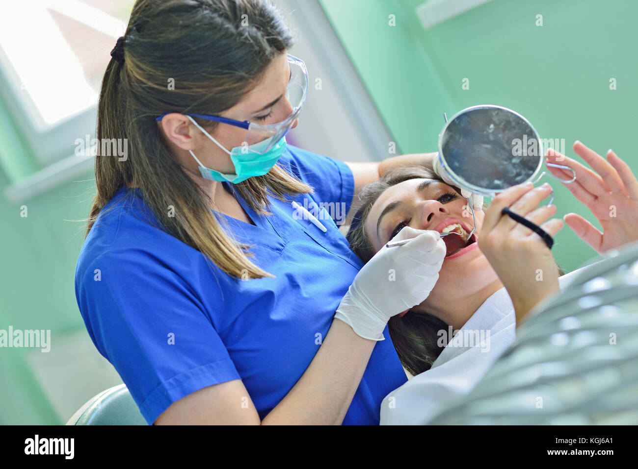 people, medicine, stomatology and health care concept - happy female dentist checking patient girl teeth - Stock Image