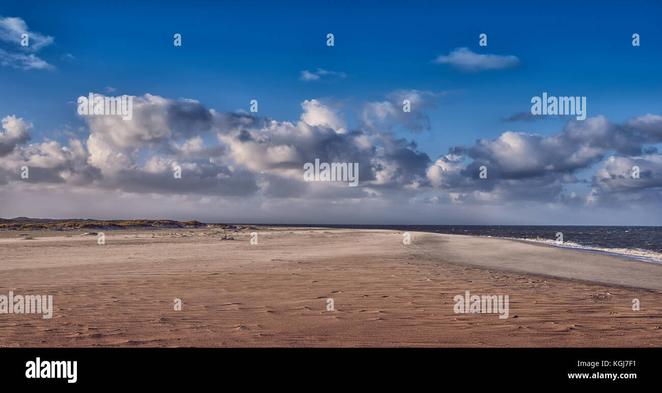 Deserted sandy beach with gentle waves breaking along the shoreline under a cloudy blue sky idyllic for a summer - Stock Image