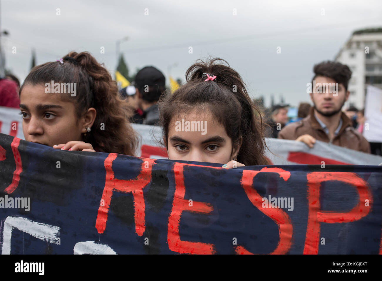 Athens, Greece. 08th Nov, 2017. Girls hold a banner as refugees are marching towards the German Embassy in protest - Stock Image