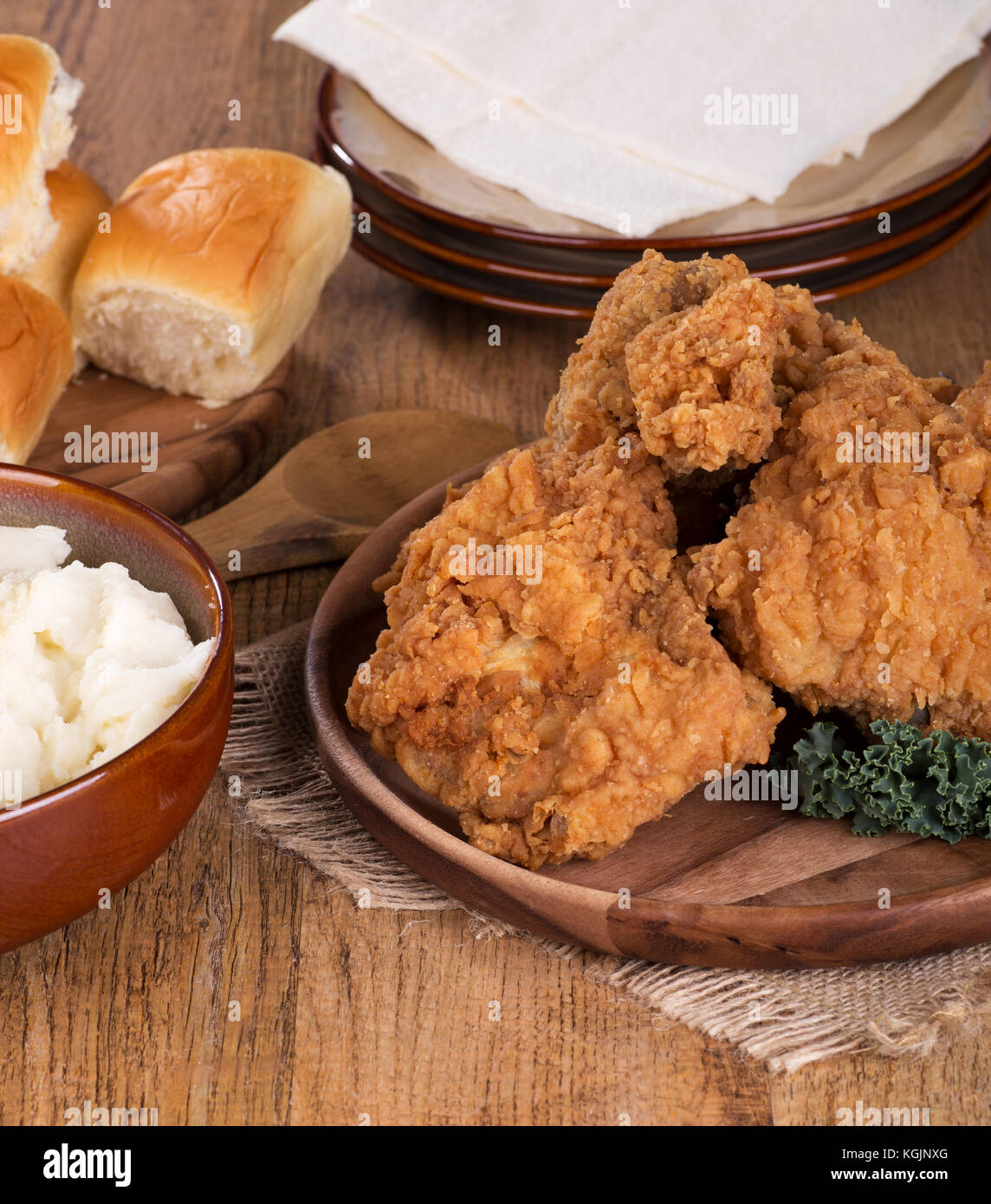 Fried chicken on a platter with mashed potatoes and rolls - Stock Image