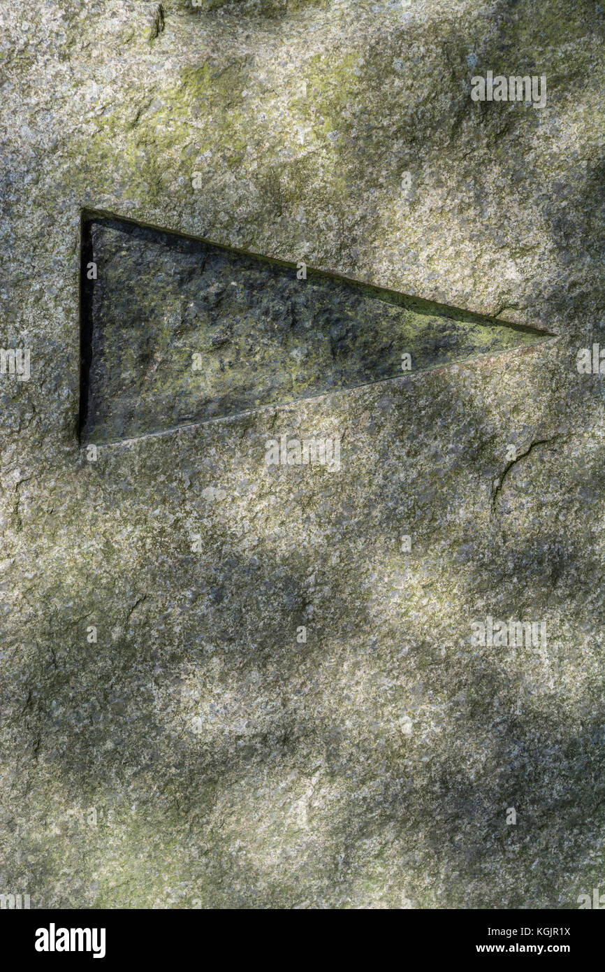 Directional arrow carved into a stone block on a country